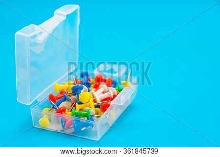 Plastic Box With Multi-colored Pushpins On Blue Background. Side View With Selective Focus.