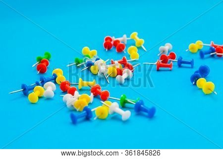 Multi-colored Pushpins Scattered Over A Turquoise Background. View From The Side.