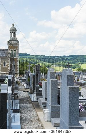 Brittany, France, June 2017. Portrait Shot Of Old Cemetery With  Headstone In A Row With Green Meado