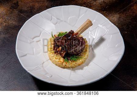 Lamb With Bulgur And Balsamic Sauce. Lamb On The Bone, Bulgur, Balsamic Cream, Arugula And Zucchini.