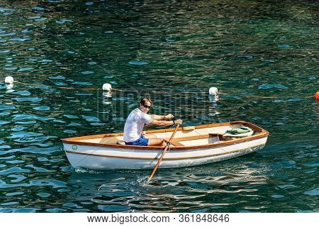 Gulf Of La Spezia, Liguria, Italy - July 21th, 2019: A Man On A White Small Wooden Rowboat In The Gr