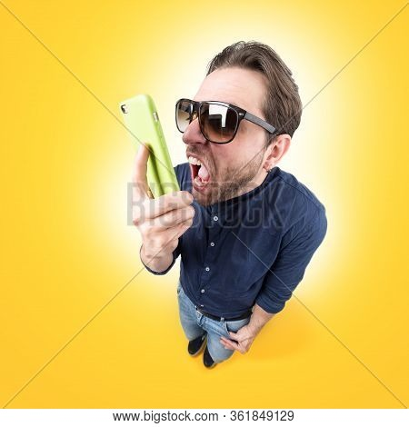 Funny Young Man Screaming On His Mobile Phone Wear A Pair Of Sun Glasses On Color Background