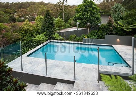Modern Swimming Pool With A Glass Fence On The Tile Floor Covered With A Garden  With Green Trees, T