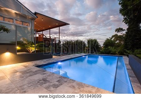 Modern House With A Pool At Evening Or In The Morning, Which Illuminated With Yellow Lights On The W