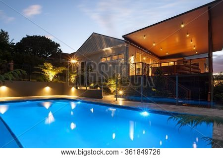Hotel With Flashing Lights Around The Pool  At Night With Light Sky , There Are Dark Areas Around Th