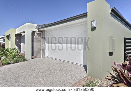 Garage Entrance Of Luxury House Design, Sky Is Blue And No Clouds Can See, Garden Has Green Plants,