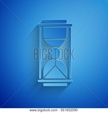 Paper Cut Old Hourglass With Flowing Sand Icon Isolated On Blue Background. Sand Clock Sign. Busines