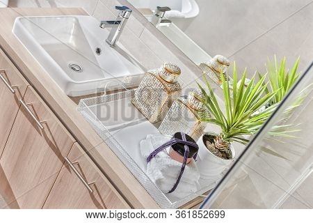 High Angle View  Of The Silver Steel Tap And White Sink With A Mirror  On The Wall Beside A Fancy Pl