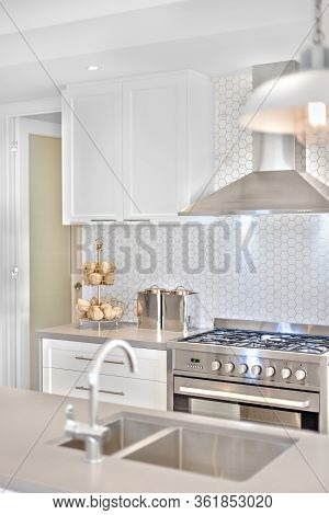 Modern Kitchen Stove With Some Fancy Items On The Counter Top, There Is Blurred Tap And Sink Before