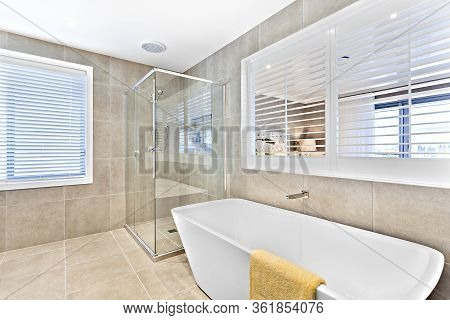 White Washbasin With A Yellow Towel And A Glass Panel Shower Area With Tiles, Floor And Wall In The
