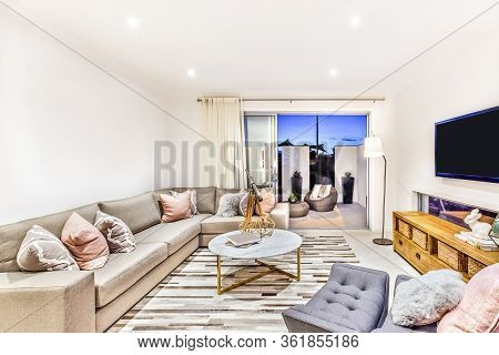 Luxurious Living Room With Sofas And Pillows Beside An Entrance, There Is A Round Table Middle Of Th