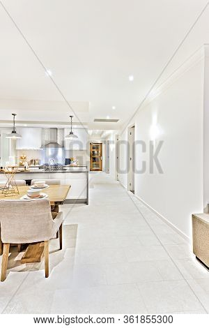 Modern Living Room Interior At Night With Flashing  Lights Through The Hallway Beside Dining Area An