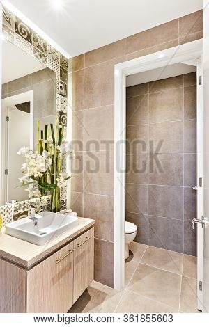 Luxury Bathroom With  An Open Door To A Toilet  Which Covered With A Wall Tile And Floor Beside A Mi