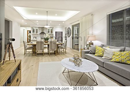 Modern Living Room Including Sofas, Chairs And Tables Beside The Kitchen And Dining Room Illuminated