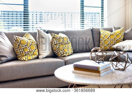 Yellow And Grey Color Pillows On The Sofa Beside A Window That Spreads The Sunlight In To The Room W