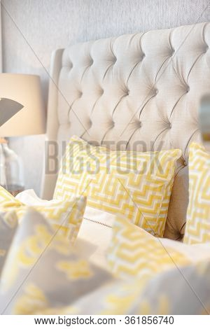 Yellow Pillows With A Maze Art On The Modern  Bed Closeup With A Working Table Lamp In A Luxury Hous