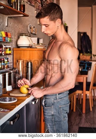 Young Shirtless Man Cutting An Apple In Kitchen