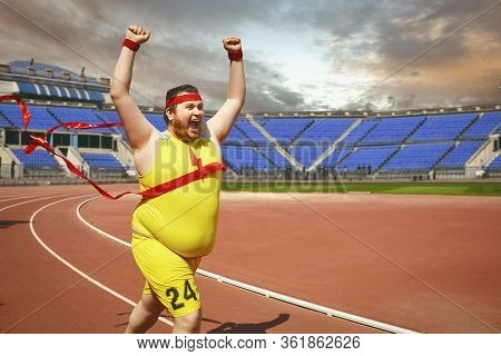 A Fat Man Runs To The Finish Line On The Track.