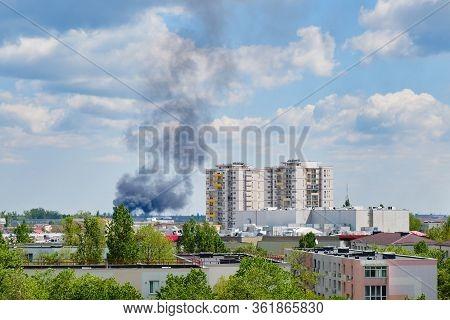 Black Heavy Smoke Cloud Near Apartment Building In Residential Area Of Bucharest, Romania, On A Sunn
