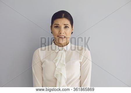 Tense Young Woman Looking At Camera On Gray Wall