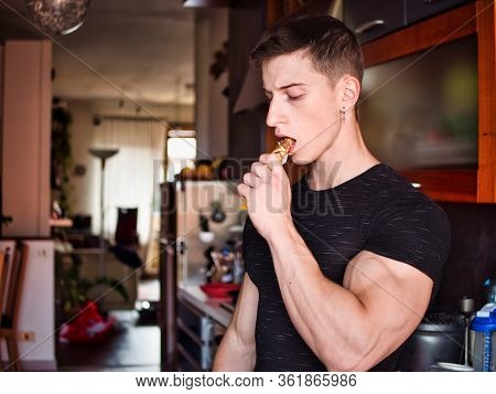 Muscular Young Man Eating Cereal Bar, Looking At Camera Standing,