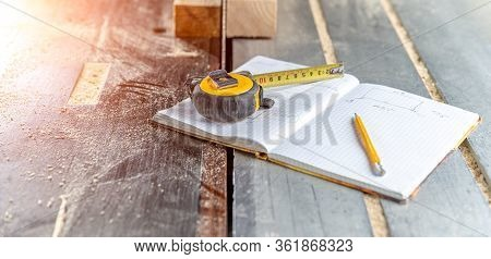 Draw Prepared Wood Products In A Workbook In A Joinery. Tape Measure, Pencil And Notebook On The Tab