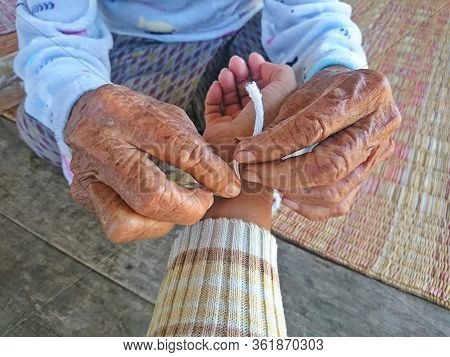 Grandma Tied The Wrist To The Sacred Thread To The Grandchildren ,to Be Auspicious Is A Culture Of T