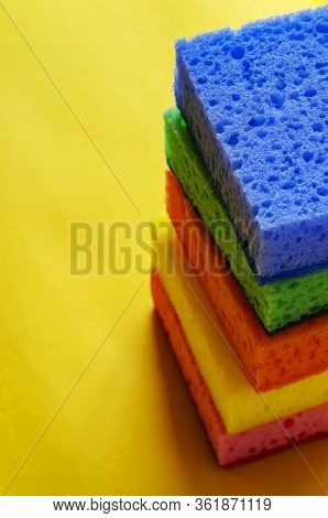 Kitchen Porous Sponges. A Stack Of Multi-colored Kitchen Sponges On A Yellow Background. A Set Of Ne