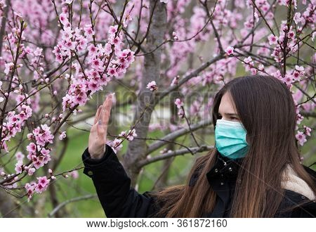 Pretty Girl With Mask On Face Walking Beside Blooming Tree And Showing Stop Sign With Hand. Spring A
