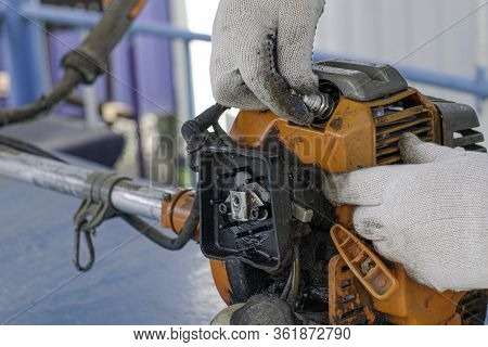 The Master In Working Gloves Repairs The Engine Of An Old Gas Trimmer, Unscrews The Spark Plug