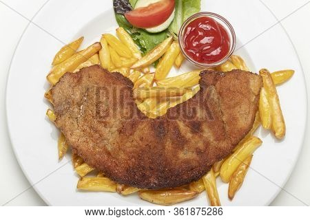 Wiener Schnitzel With French Fries On A Plate