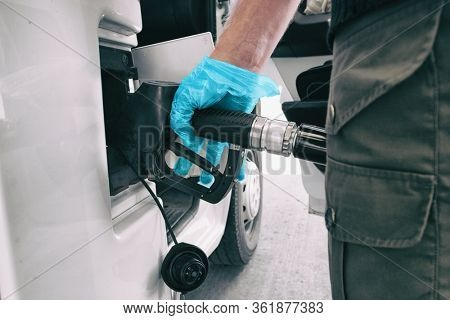 Coronavirus gas oil prices dropping man pumping gasoline at gas station wearing medical blue glove as COVID-19 spreading safety protection for touching germs.