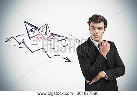 Pensive European Businessman Standing Near Grey Wall With Sinking Paper Boat And Declining Graph Dra