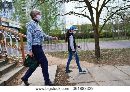 woman and child girl walks down the street during the day, a pedestrian walkway and buildings with apartments, a residential area, a medical mask on their faces protects against viruses and dust