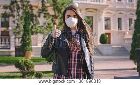 In The Middle Of Empty Street Woman With A Protective Mask Suggesting To People To Wearing Mask To S