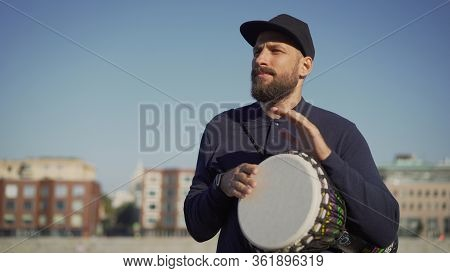 A Street Musician Plays Tom-tom On A Drum. A Musician Stands On The Street And Holds A Drum Tomtom I
