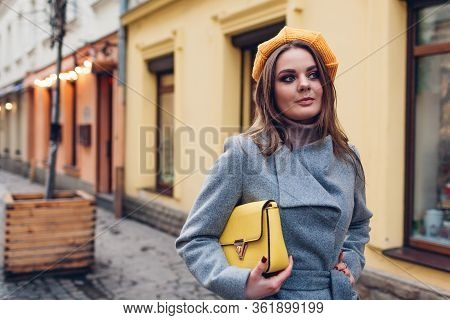 Portrait Of Stylish Young Woman Wearing Yellow Beret Coat Holding Purse On Street. Spring Fashion Fe