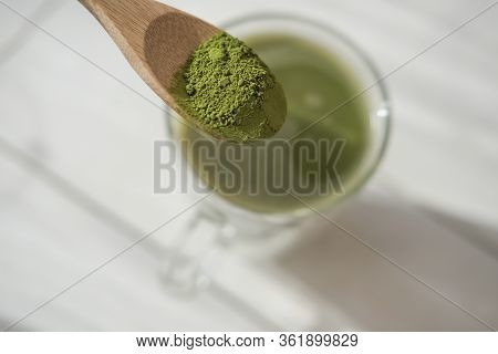 Matcha Latte In A Glass Mug And Matcha Powder In Wooden Spoon. Healthy Drinks Concept. Modern Fashio