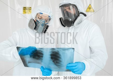 Epidemiologists In Respirators Examine The Patients Pneumonia On A Radiograph Covid-19. Concept Of C