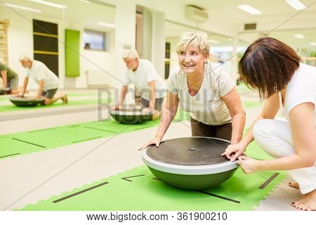 Physiotherapist helps senior woman with fitness training with the Bosu Ball in the gym