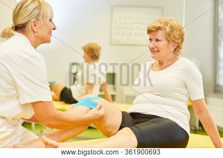 Naturopath attaches Kinesio Tape for knee pain in senior patient in rehab