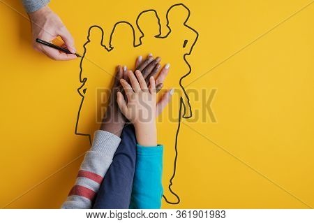 Male Hand Drawing Silhouette Of A Family With Black Marker, With Hands Of Wife And Two Kids Inside T
