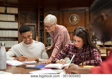Senior teacher helping young african man at the library. Group of university guys and girl sitting at desk while mature professor helping them. Group of multiethnic high school students studying.