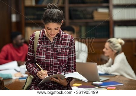 Concentrated young woman standing in library and writing on notebook. University student completing assignment to submit while standing in library. Girl studying with copy space.