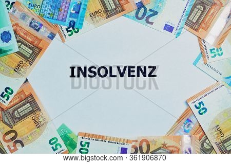 The German Word For Insolvency Is Printed On A White Paper, Around Are Lying A Lot Of Different Euro