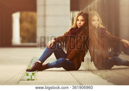 Happy young fashion woman sitting on street sidewalk  Stylish female model in brown leather fringe suede jacket and dark blue jeans