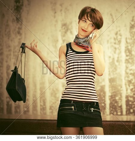 Happy young fashion woman with handbag calling on cell phone Stylish female model with pixie hair in striped tank top and denim skirt