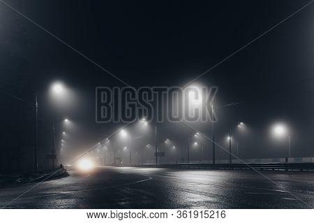 Foggy Misty Night Road Illuminated By Street Lights