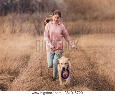 Playful dog running with teenage girl outside