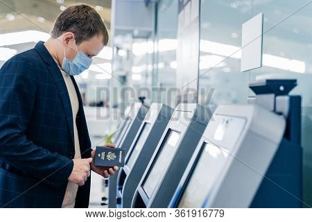 Sideways Shot Of Man Poses At Self Check In Desk In Airport, Holds Passport, Going To Register For F